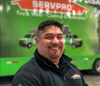 man in front of ta SERVPRO trailer