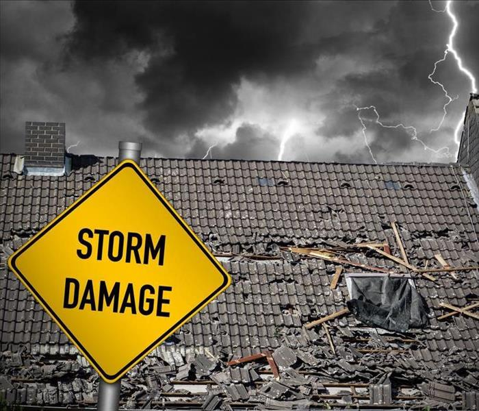 A damaged roof from a thunderstorm with a sign that spells Storm Damage