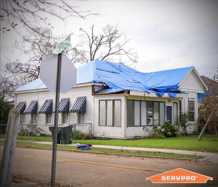 a home with a blue tarp secured to the damaged roof.